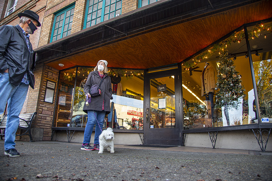 A couple and their dog go window shopping on 1st Street in Downtown Newberg