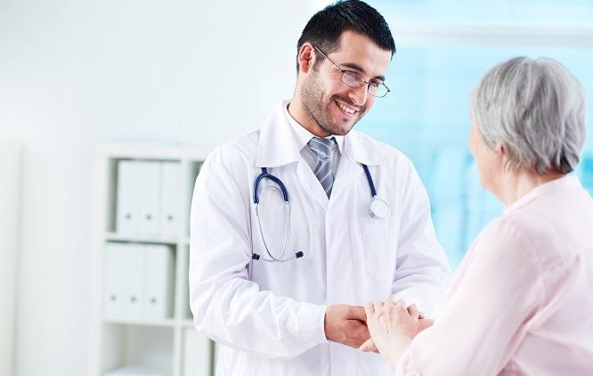 Médico segurando a mão de uma paciente