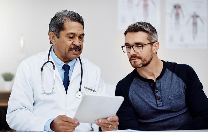 médico sentado ao lado de um homem mostrando papéis e explicando algo