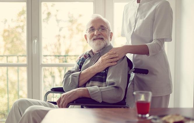 enfermeira acompanhando um paciente idoso sentado em uma cadeira de rodas