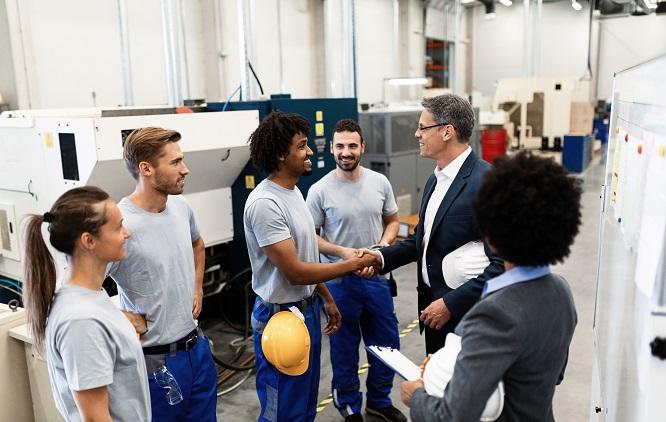 Funcionarios em uma fábrica cumprimentando um homem