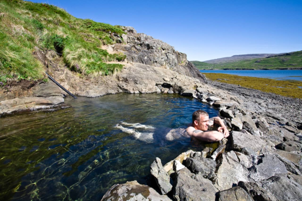 A man soaking in Hellulaug pool in The Westfjords