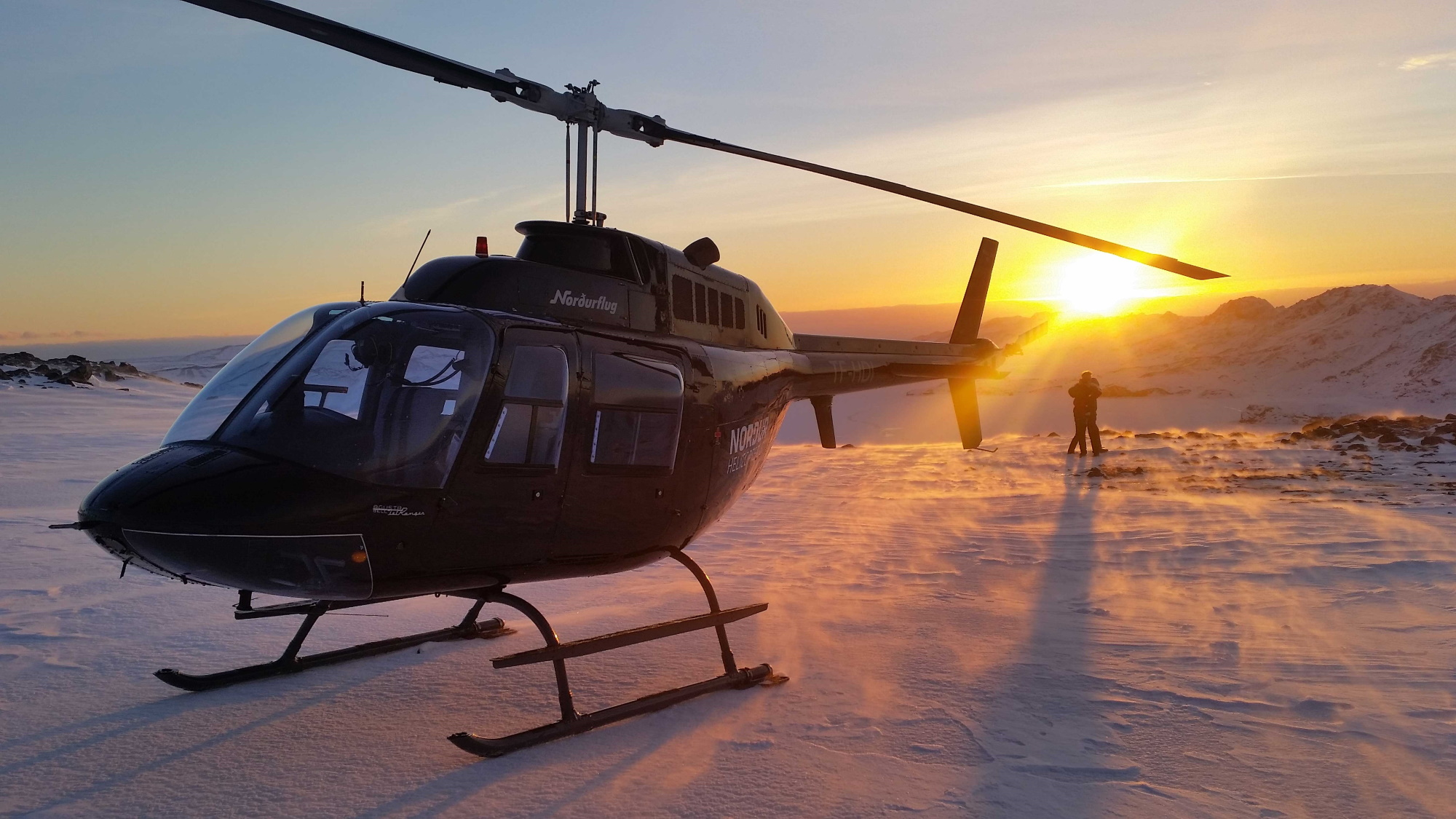 A helicopter in snow at sunset.