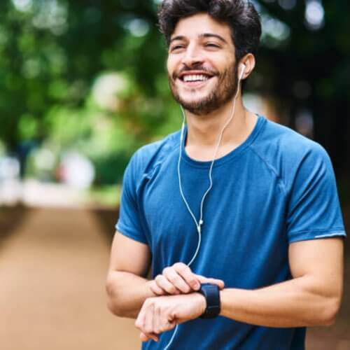 Smiling man using smart watch and taking a break from working out