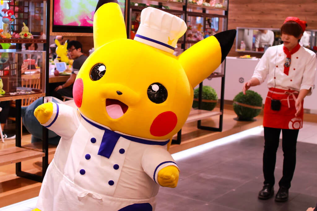 Chef Pikachu walking outside with a waiter behind him.